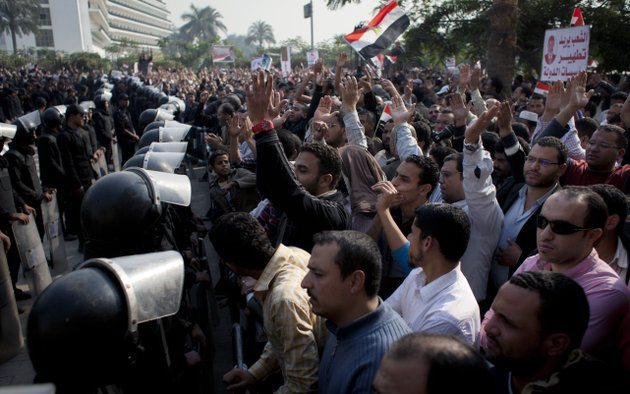 supporters-of-egyptian-president-mohammed-morsi-chant-slogans-as-riot-police-left-stand-guard-in-front-of-the-entrance-of-egypts-top-court-in-cairo-egypt-sunday-dec-2-2012-egypts-top-court-announced-on-sunday-the-suspension-of-its-work-indefinitely-to-protest-psychological-and-physical-pressures-saying-its-judges-could-not-enter-its-nile-side-building-because-of-the-islamist-presidents-supporters-gathered-outside-arabic-on-the-poster-right-reads-the-people-want-to-purify-the-states-institutions