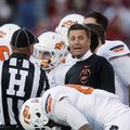 Oklahoma State coach Mike Gundy talks to an official during a timeout in the third quarter of an NCA...