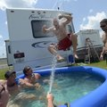Ted Georges, of Columbus, Ohio, jumps into a pool from the top of a recreational vehicle parked in t...