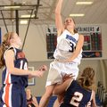 McKinzie James, Rogers High, takes the ball to the basket Saturday over Rogers Heritage's Ashley War...