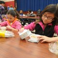 Jocelyn Martinez, 6, left, and big sister Vasti Martinez, 9, pour milk over their Frosted Flakes on ...
