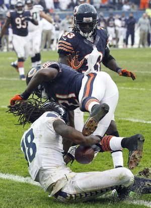 Seattle Seahawks receiver Sidney Rice catches a touchdown pass from quarterback Russell Wilson in overtime against the Chicago Bears as Bears safety Major Wright defends Sunday at Soldier Field in Chicago.