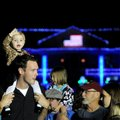 McKayla Caywood, 18 months, waves as she sits on the shoulders of her father, Clay Cawood, to watch ...