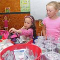 Caroline Long, 9, right, assists Hailey Prendas, 6, as she looks through possible gifts for her mom,...
