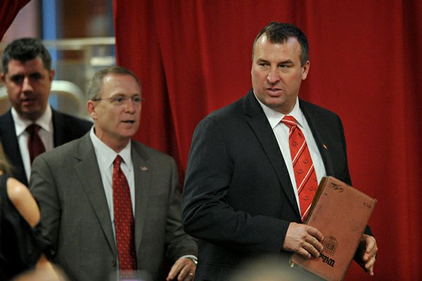 Arkansas football coach Bret Bielema, right, and Arkansas athletics director Jeff Long walk into the Raymond Miller Room on Wednesday, Dec. 5, 2012, for a press conference announcing Bielema as the Razorbacks' football coach.