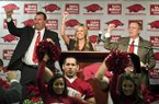 Bret Bielema (left), Jen Bielema (center) and Jeff Long lead a hog call on Wednesday.