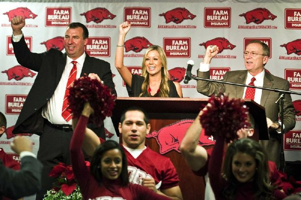 New Arkansas head coach Bret Bielema, left, his wife, Jen, center, and athletic director Jeff Long, right, Call the Hogs during an NCAA college football news conference in Fayetteville, Ark., Wednesday, Dec. 5, 2012. (AP Photo/April L. Brown)
