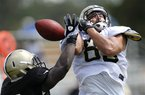 New Orleans Saints linebacker Lawrence Wilson, left, breaks up a pass intended for tight end Jake Byrne (82) during NFL football training camp in Metairie, La., Wednesday, Aug. 1, 2012. (AP Photo/Gerald Herbert)