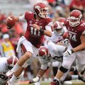 STAFF PHOTO ANDY SHUPE -- Arkansas quarterback Brandon Allen is tripped up by Alabama defensive line...