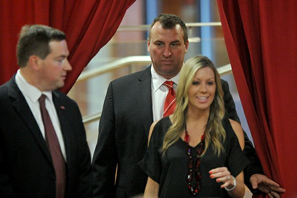 Arkansas football coach Bret Bielema follows his wife, Jen, into the Raymond Miller Room on Wednesday at Donald W. Reynolds Razorback Stadium.