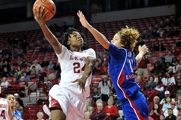 NWA Media/MICHAEL WOODS --12/06/2012-- Arkansas forward Quistelle Williams drives past Kansas defender Monica Engelman to score on a fast break during the first half of Thursday night's game at Bud Walton Arena in Fayetteville.