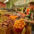 Jeff Alvine, staff member at the Ozark Natural Foods in Fayetteville, puts out fresh fruit Wednesday...