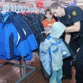 Jonathan Pike, right, an officer with the Springdale Police Department, helps Michael Howard, 5, try...