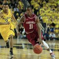 Arkansas guard BJ Young (11) drives around Michigan guard Trey Burke (3) during the first half of an...