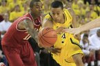 Arkansas guard BJ Young (11) reaches in and fouls Michigan guard Trey Burke (3)during the second half of an NCAA college basketball game in Ann Arbor, Mich., Saturday, Dec. 8, 2012. (AP Photo/Carlos Osorio)