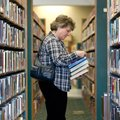 Diana Ashley of Rogers peruses through shelved books Wednesday at the Rogers Public Library. Area li...