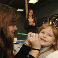 Sarah Emison with the Northwest Arkansas Mercy Family YMCA paints a holiday design Saturday on the c...