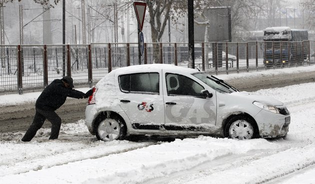a-man-pushes-a-car-on-a-snow-covered-street-in-belgrade-serbia-sunday-dec-9-2012-freezing-temperatures-and-heavy-snowfall-have-killed-at-least-5-people-and-caused-travel-chaos-across-the-balkans