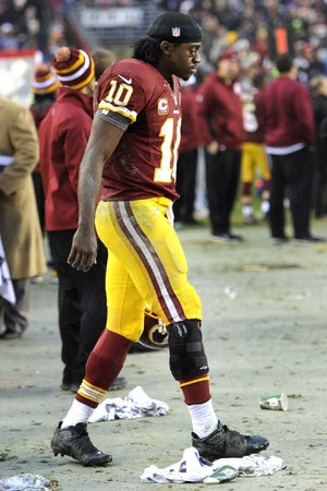 Washington Redskins rookie quarterback Robert Griffin III walks on the sideline with a brace on his knee during overtime Sunday afternoon against the Baltimore Ravens in Landover, Md. Griffin sprained his right knee in fourth quarter of the Redskins' 31-28 overtime victory over the Ravens.