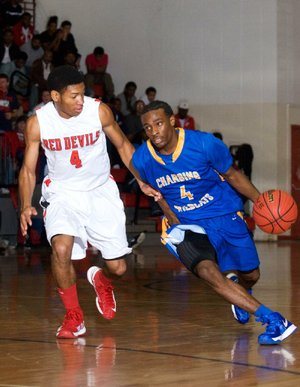 North Little Rock's Dayshawn Watkins (right) dribbles past Jacksonville's Justin McCleary (4) during the Charging Wildcats' 60-52 victory over the Red Devils on Tuesday in Jacksonville.