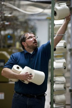 Mike Hartman moves spools of thread at FesslerUSA apparel in Orwigsburg, Pa., in October. The U.S. Commerce Department reported Tuesday that wholesale businesses increased stockpiles in October but saw their sales fall, a mixed sign for economic growth.