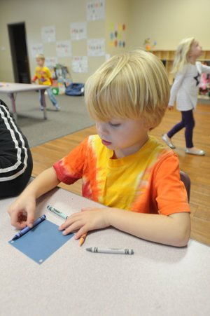 Ryan Fritsche decides how to arrange his crayons to frame his Christmas tree ornament Friday at Just Like Home Childcare-West in Fayetteville.