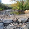 Riders sometimes cross Lee Creek in knee-deep water on the Fossil Flats Trail. The stream, seen in O...