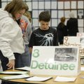 Jeremy Kalminski, 12, shows his mother Becky the research reports he and his classmates completed fo...