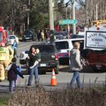 Parents walk away from the Sandy Hook Elementary School with their children following a shooting, Fr...