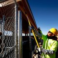 Jose Macias with Geels Paint paints the overhang on one of the dugouts for Field 6 on Thursday at th...