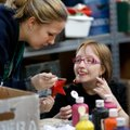 Nicole Rose, (above) left, a volunteer, lends a helping hand to Claire Ironside while she paints a C...