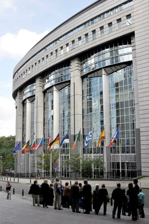 Tourists view the glassy facade of the Paul-Henri Spaak Building, home of the European Parliament in Brussels.