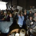Darrell Seaman, center, holds up a metal chair Friday as auctioneer Mike Price of Price Auction Mark...