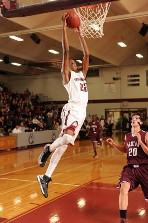 Dashaun Stark, a Springdale senior, dunks the ball as Benton center Josh Bowling trails the play during the first half Friday at Springdale High.