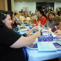 "Jennifer Jackson and other members of Temple Shalom use a ""shamash"" or ""helper candle"" to light the ..."