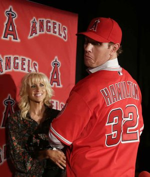 Free-agent outfielder Josh Hamilton models his new Los Angeles Angels jersey for the crowd as his wife, Katie, looks on during an introductory news conference Saturday in Anaheim, Calif.