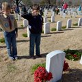 Noah Toto, left, age 10, and Eddie Hunter, age 10, both from Rogers, salute after putting a wreath o...