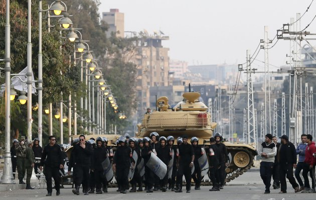egyptian-riot-police-walk-past-a-military-tank-guarding-the-presidential-palace-in-cairo-egypt-sunday-dec-16-2012-key-egyptian-rights-groups-called-sunday-for-a-repeat-of-the-first-round-of-the-constitutional-referendum-alleging-the-vote-was-marred-by-widespread-violations-islamists-who-back-the-disputed-charter-claimed-they-were-in-the-lead-with-a-majority-of-yes-votes