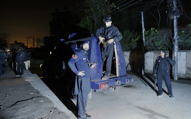 pakistani-police-officers-gather-beside-an-armored-vehicle-near-the-site-of-rocket-attack-by-militants-in-peshawar-pakistan-on-saturday-dec-15-2012-militants-fired-three-rockets-at-an-airport-in-the-northwestern-pakistani-city-of-peshawar-on-saturday-night-killing-several-people-and-wounding-dozens-officials-said