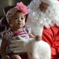 Winter Hill, 9 months, looks to her mother Adaline as she has her photo taken Saturday with Santa Cl...