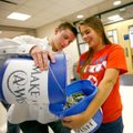 Stokes Wenzler, Deca vice president, dumps donated money into the bucket Friday held by club preside...