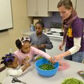 Ally Mrachek, a FoodCorps Service Member, right, works with Vyleria Hull, from left, 3, Syveria Hull...