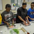 Kentrell Hull, 10, from left, Syveria Hull and Roderick Hull, 13, work on preparing their chicken di...