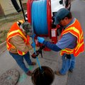 Johnny Lunsford, left, and Pat Sharp, both with Rogers Water Utilities, work to lower a hose into th...