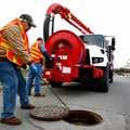 Johnny Lunsford, left, removes the manhole cover while Pat Sharp, both with Rogers Water Utilities, ...