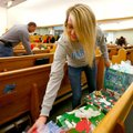 Ashley Wiedenhoeft, 17, helps organize gifts inside the sanctuary on Sunday at St. Joseph Catholic C...