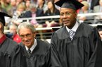 NWA Media/MICHAEL WOODS --12/15/2012-- Former University of Arkansas basketball player Darrell Walker, right, who played with the Razorbacks from 1980-83 is accompanied by former University of Arkansas basketball coach Eddie Sutton who coached at Arkansas from 1974-1985, as they participate in the fall commencement ceremony at Barnhill Arena in Fayetteville on Saturday morning. Sutton had the honor of presenting Walker with his degree. Over 800 undergraduate, graduate and law students who completed their studies during the summer or fall semesters will took part in the commencement ceremony.