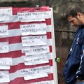 A man pays respects Monday in Newtown, Conn., near a U.S. flag with the names of victims on a makesh...