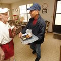 Leonard Lopez, a volunteer driver with Fayetteville's Meals on Wheels program, right, hands out Chri...