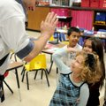 Scott Walker, with Mid-America Karate, gets a high-five from Amore Derossi, 5, Monday after she prac...
